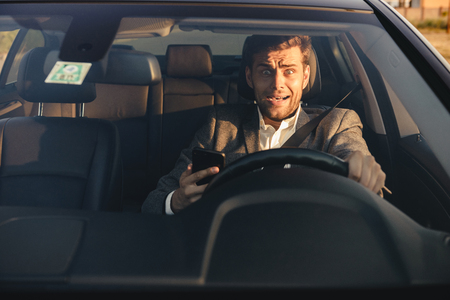 Portrait of a scared young business man getting into car accident while driving, holding mobile phone
