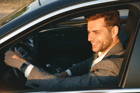 Happy bussinesman in suit driving his car