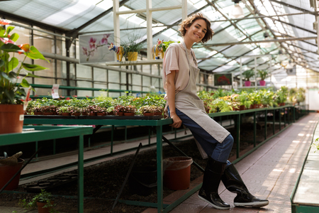 Image of attractive cute woman gardener standing over flowers plants in greenhouse