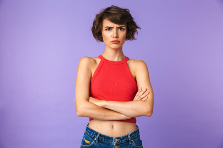 Image closeup of young displeased woman 20s in casual wear frowning and standing with arms folded isolated over violet background