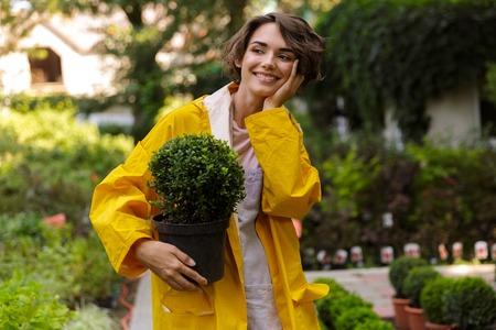 Image of beautiful cute woman gardener standing over flowers plants in greenhouse holding plants Standard-Bild - 108838689
