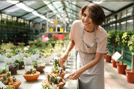 Image of attractive cute woman gardener standing over flowers plants in greenhouse working Standard-Bild - 108838779