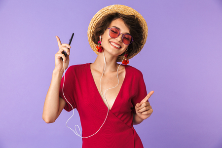 Image of adorable brunette woman 20s in straw hat and earphones listening to music on cell phone isolated over violet background Stock Photo