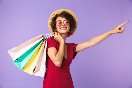 Image of excited brunette woman 20s in straw hat holding colorful paper shopping bags and pointing at copyspace isolated over violet background Stock Photo