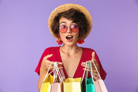 Image of excited brunette woman 20s in straw hat holding colorful paper shopping bags isolated over violet background Stock Photo