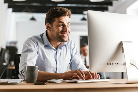 Image of Funny business man using computer while sitting by the table in office