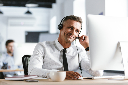 Photo of joyful operator man 30s wearing office clothes and headset smiling while working on computer in call center