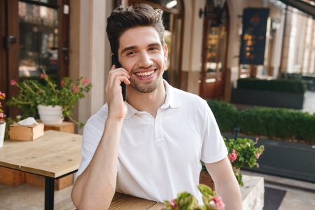Image of young cheerful man sitting in cafe outdoors while talking by mobile phone. Reklamní fotografie