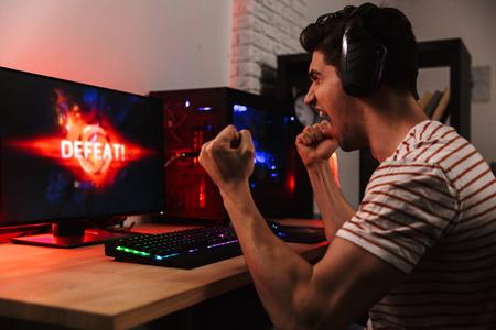 Seitenansicht des schreienden unzufriedenen Spielers, der zu Hause Videospiele auf dem Computer spielt Standard-Bild
