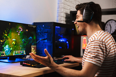 Image of cheerful gamer man playing video games on computer wearing headphones and using backlit colorful keyboard