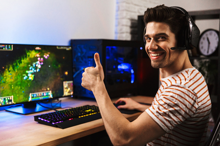 Portrait of joyful gamer guy in headphones playing video games on computer and showing thumb up