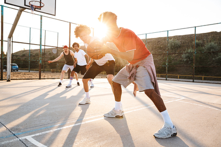 Group of young cheerful multiethnic men basketball players playing basketball at the sport ground