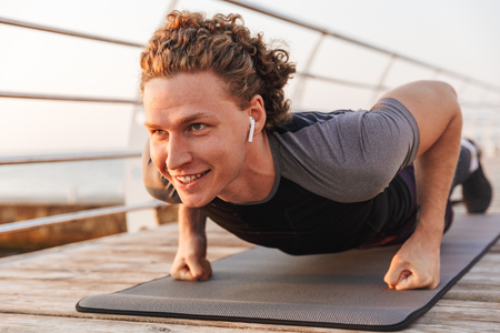 Smiling young sportsman in wireless earphones doing push ups on a fitness mat outdoors Standard-Bild - 108965936