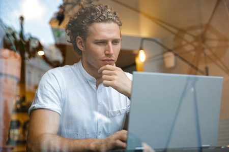 Serious curly business man using laptop computer while sitting by the table in cafe