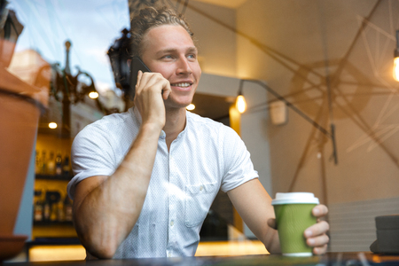 Smiling curly business man talking by the smartphone and drinking coffee while sitting by the table in cafe