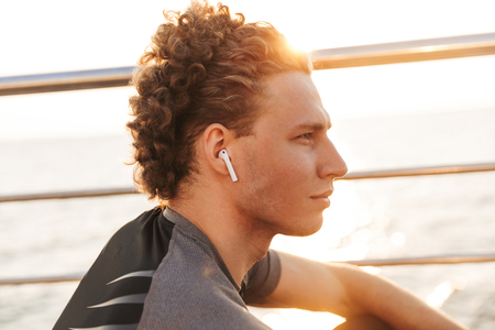 Close up of a handsome young sports man listening to music with wireless earphones outdoors