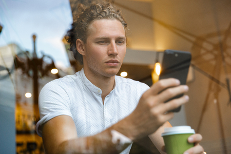 Serious curly business man using smartphone and drinking coffee while sitting by the table in cafe Stock Photo