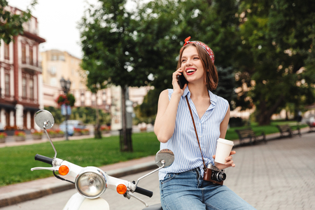 Cheerful young hipster woman talking by smartphone and looking away while sitting on scooter outdoors 版權商用圖片
