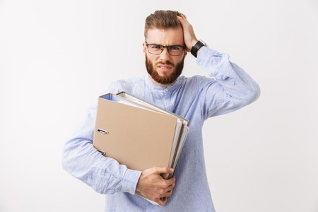Portrait of a tired young bearded man standing isolated over white, holding folders