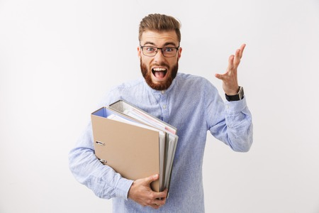 Portrait of a tired young bearded man standing isolated over white, holding folders, screaming Stock Photo