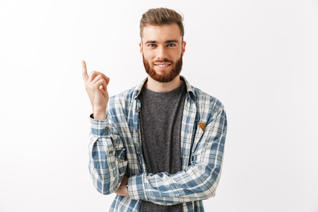 Portrait of a smiling young bearded man standing isolated over white, pointing finger up
