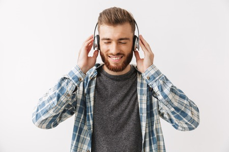 Happy bearded man in shirt and headphones listening music with closed eyes over grey background