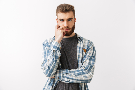 Portrait of a serious young bearded man standing isolated over white, thinking