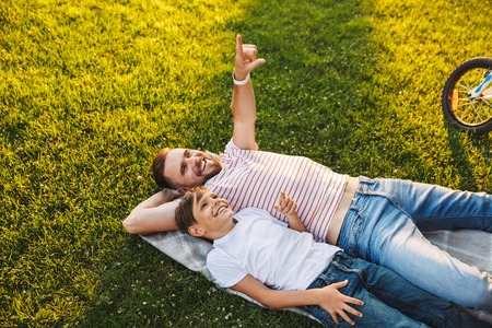 Image of happy young man father have a rest with his son outdoors in park pointing. Stok Fotoğraf