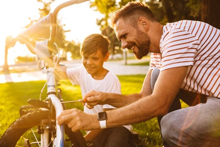 Happy father and his son having fun together at the green park, fixing bicycle together