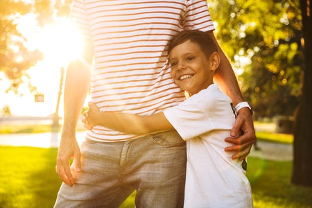 Happy little boy hugging his dad while standing at the park