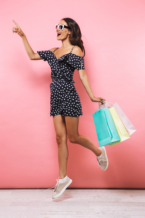 Photo of cheerful woman jumping isolated over pink background holding shopping bags pointing.