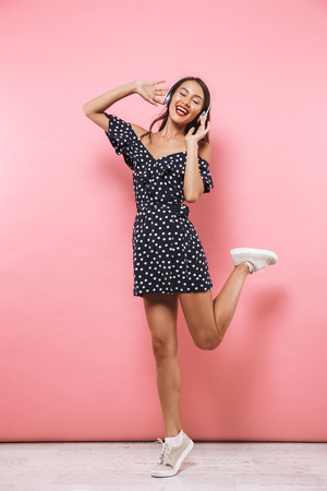 Full length image of Happy brunette woman in dress and headphones listening music while jumping and enjoys with closed eyes over pink background