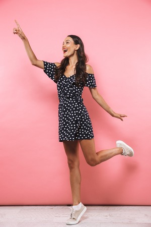 Full length image of Pleased brunette woman in dress jumping while pointing and looking away over pink background Foto de archivo