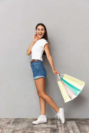 Image of happy emotional woman standing isolated over grey wall background holding shopping bags.