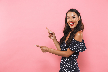 Side view of cheerful brunette woman in dress pointing on copyspace and looking at the camera over pink background Foto de archivo