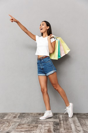 Photo of young happy woman holding shopping bags isolated over grey background pointing. Banque d'images - 111963013