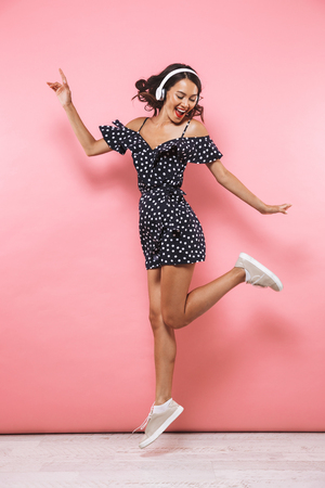 Full length image of Cheerful brunette woman in dress and headphones listening music while jumping over pink background