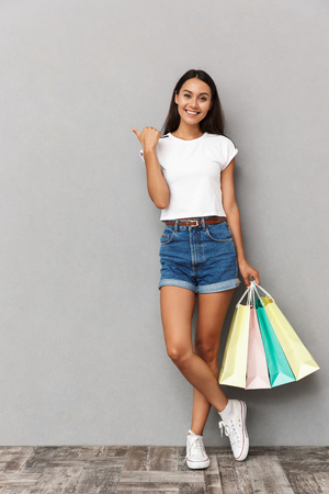 Image of happy emotional woman standing isolated over grey wall background holding shopping bags pointing.