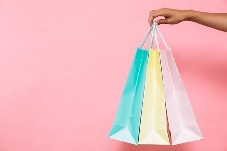 Abgeschnittenes Bild einer Frau, die Pakete mit Einkäufen über rosa Hintergrund hält Standard-Bild