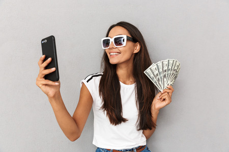 Photo of charming woman with long dark hair in sunglasses smiling while holding fan of dollar cash and smartphone isolated over gray background in studio