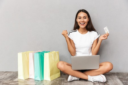 Image of happy emotional woman sitting near shopping bags isolated over grey wall background holding credit card using laptop computer.