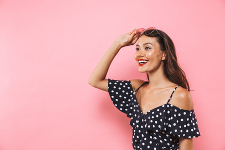 Happy brunette woman in dress take off sunglasses and looking away over pink background Banco de Imagens