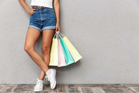 Cropped photo of woman standing isolated over grey wall background holding shopping bags. Stock Photo