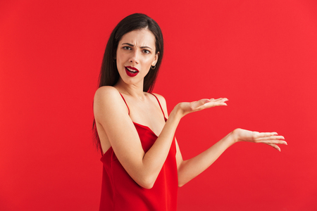Portrait of a confused young woman in dress isolated over red background, pointing at copy space