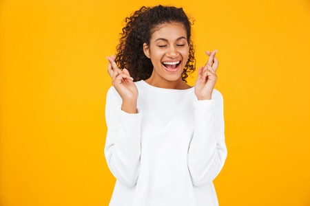 Portrait of a pensive young african woman standing isolated over yellow background, holding fingers crossed for good luck