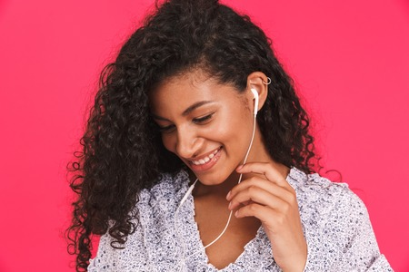 Portrait of a smiling young african woman in summer dress standing isolated over pink background, listening to music with earphones 写真素材