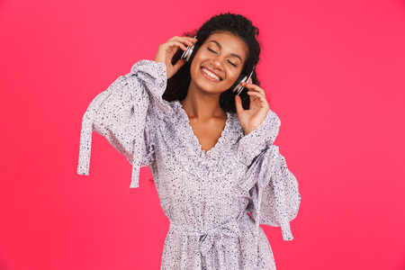 Portrait of a happy young african woman in summer dress standing isolated over pink background, listening to music with headphones 写真素材