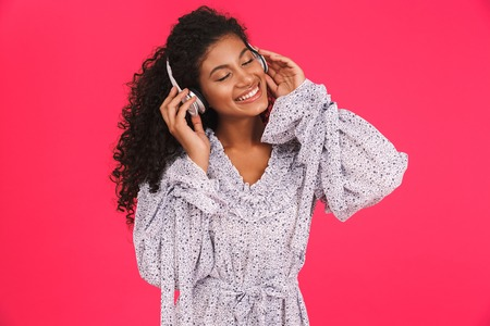 Portrait of a smiling young african woman in summer dress standing isolated over pink background, listening to music with headphones