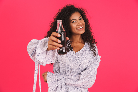 Portrait of a cheerful young african woman in summer dress standing isolated over pink background, showing glass bottle of fizzy drink
