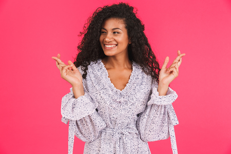 Portrait of a happy young african woman in summer dress standing isolated over pink background, holding fingers crossed Stock Photo